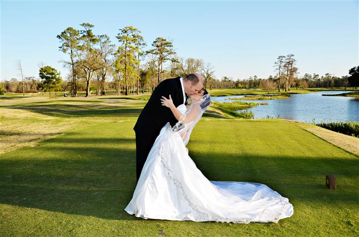 Groom kissing bride on tee box of golf course